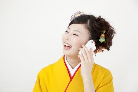 early 20s: Kimono woman to phone Stock Photo