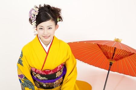 early 20s: Kimono woman smiling next to the Japanese umbrella Stock Photo