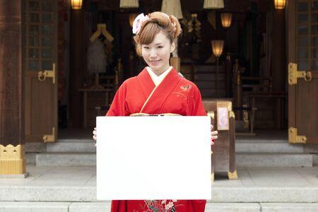 worshipping: Women kimono figure with a white board