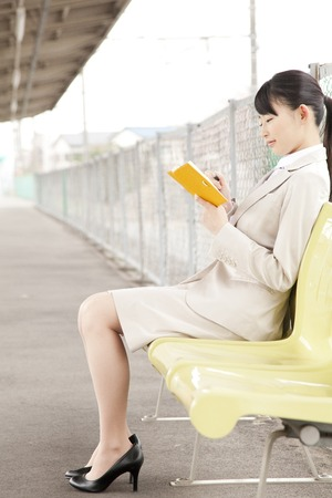 OL sit with a notebook at the station of home