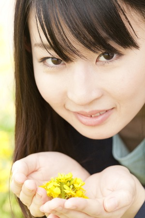 あなたの手の手のひらに菜の花を入れて女性