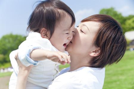 어머니는 키스하고 아이를 들어 올려하기