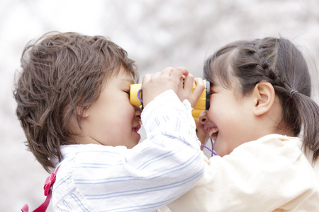 both sides: Children except the binoculars from both sides