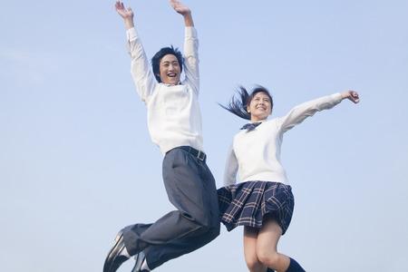 ジャンプする高校生カップル 写真素材