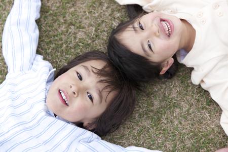 lie down: Children hand in hand, lie down on the grass Stock Photo