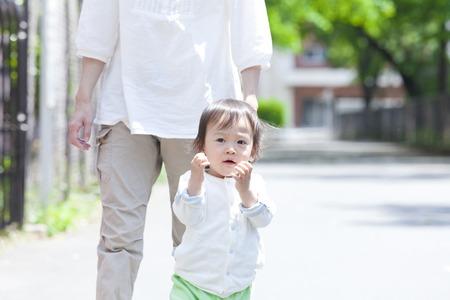 親と子は、公園の中を歩く 写真素材