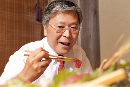 farewell party: Businessman eating sashimi Stock Photo