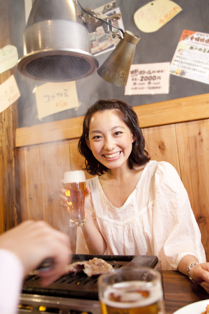 roast meat: Woman smiling with a beer