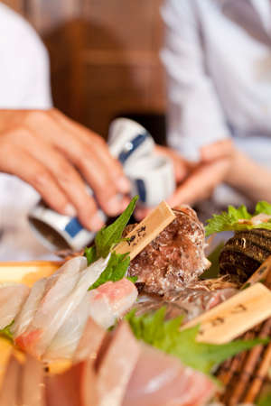 rawness: Hand of businessman to be serving sake Stock Photo