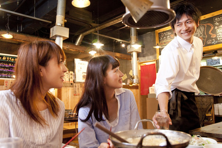 Clerk and female customers to issue a drink 写真素材
