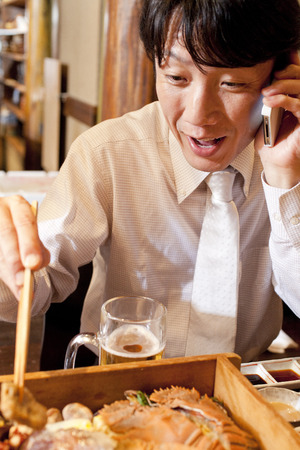 farewell party: Businessman to phone while eating cuisine Stock Photo