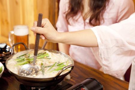 鍋をつつく女性