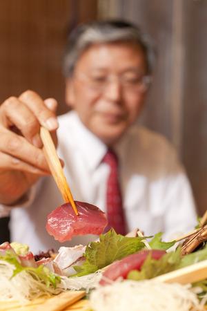 rawness: Businessman eating sashimi Stock Photo