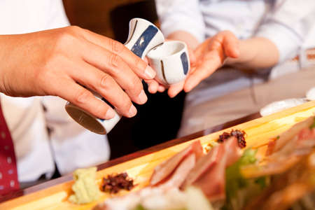 farewell party: Hand of businessman to be serving sake Stock Photo