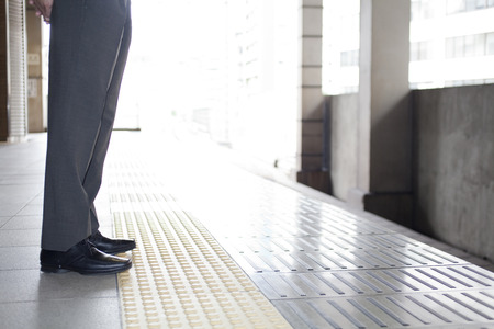 personal injury: Feet of businessman standing on train platform