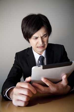 depress: Businessman surprised to see a tablet PC
