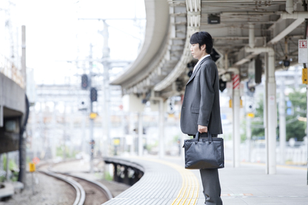 personal injury: Businessman standing on the train platform