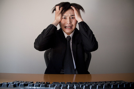 Businessmen hold their head in front of the PC Stock fotó