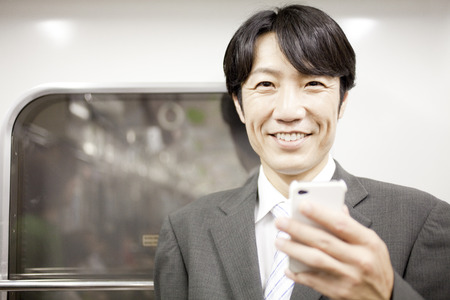 Businessman smiling with a smartphone Stock Photo
