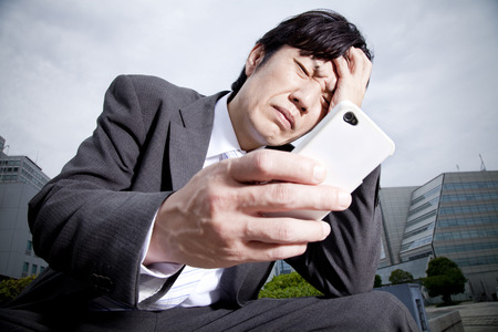 agonizing: Businessman suffering to see the smartphone Stock Photo