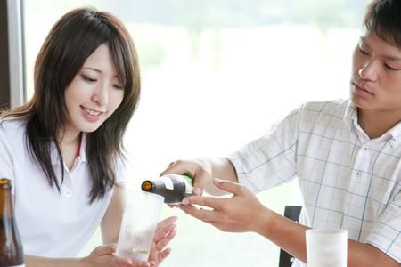 bottled beer: Men and women pour bottled beer