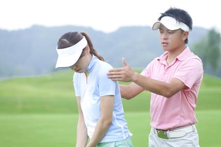 女性が男性からゴルフ レッスンを受ける