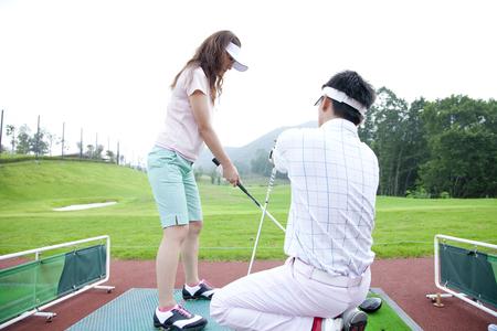 練習場でのゴルフ レッスンを受ける女性 写真素材
