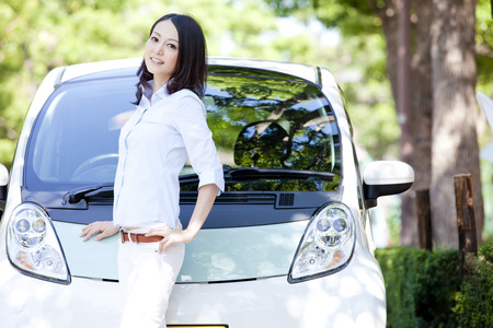 Woman smiling in front of the electric car