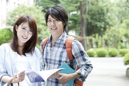 笑顔の学生は、テキストを開いてください。 写真素材