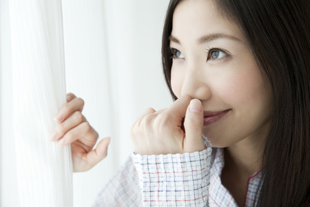 asian ancestry: Woman opening the curtain Stock Photo