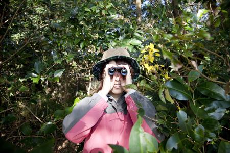 peer to peer: Las mujeres se asoman a trav�s de binoculares Foto de archivo
