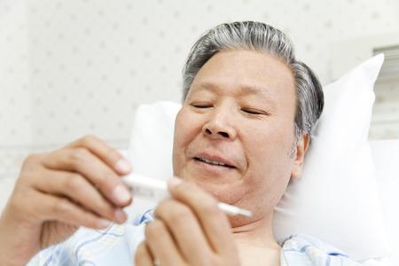 pacjent: Pacjenci uśmiech i spojrzeć na termometr