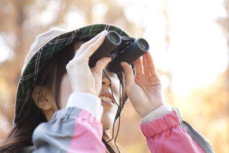 peer to peer: Women peer through binoculars