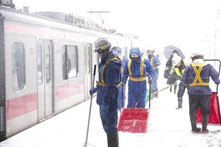 shoveling: Snow shoveling landscape in Tokyo Station Home