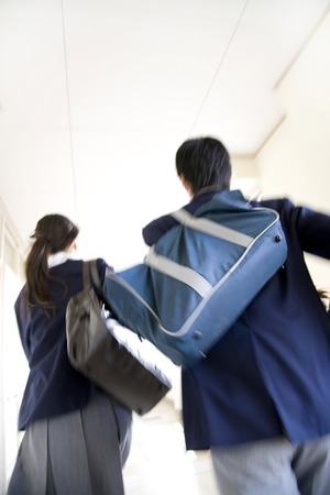 10's: Male and female junior high school students run down the hallway