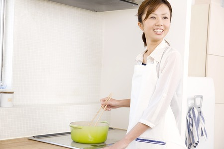 gratification: Woman cooking Stock Photo