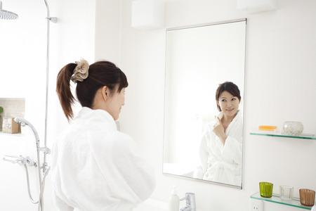 oriental bathrobe: Women look in mirror Stock Photo