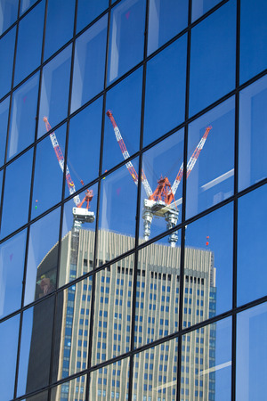 Under construction building that is reflected in the window glass