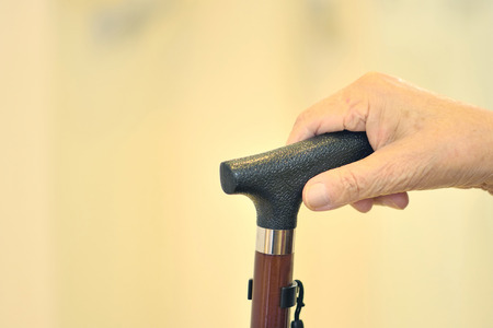 sustained: The hands of the old man caught in cane Stock Photo