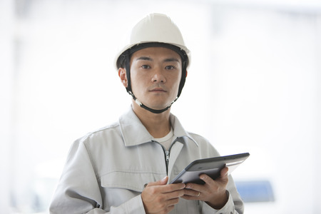 Male workers to use a Tablet PC Stock Photo