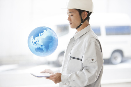 building safety: Male workers see the earth floating in the tablet PC
