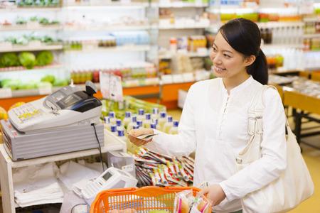 여성은 슈퍼마켓에서 쇼핑하기 스톡 콘텐츠