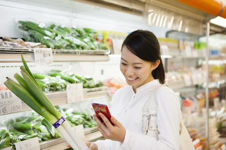 abarrotes: los compradores de las mujeres miran smartphone