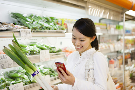 japanese cooking: Women shoppers look at Smartphone