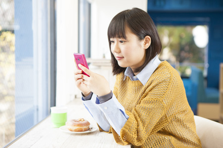 Girl to see the smartphone in a cafe Stock Photo