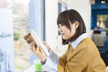 Girl reading a book in a cafe Stock Photo