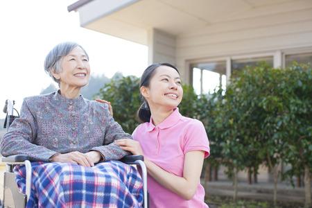 ancianos caminando: La abuela se hizo cargo y sillas de ruedas Foto de archivo