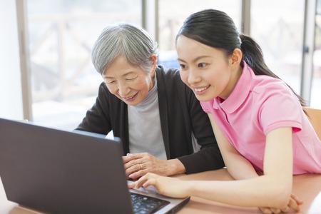seres vivos: Los cuidadores que ven el ordenador portátil y mi abuela Foto de archivo