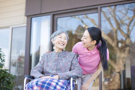 an elderly person: La abuela se hizo cargo y sillas de ruedas Foto de archivo