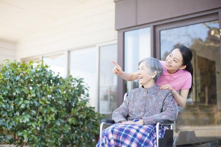 persona en silla de ruedas: La abuela se hizo cargo y sillas de ruedas Foto de archivo